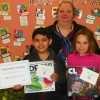 """From left, Allen Garcia-Reyes, a fifth grader, and Elizabeth Black, a third grader, both students at Aycock Elementary. Garcia-Reyes also holds the """"Honorable Mention"""" award he received for his poster being recognized at the NCSBA Conference on November 16 in the grades 3-5 category. Pam Barrier, Aycock's art teacher who worked with the students, also is shown."""