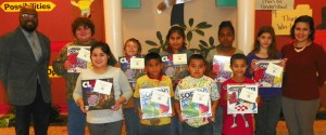 Students from Zeb Vance Elementary who created posters for the competition. They are shown with their gifts and include, front row from left, Pearla Tabor, third grader; Ian Kidd-Ponce, first grader; Uziel Sosa, second grader; and Tyreese Gibbs, first grader. On the back row, from left, are Principal Kristian Herring; Dallas Roberson, fifth grader; Damian Jones, fifth grader; Joana Ramos, fifth grader; Eliana Diaz, fifth grader; Audrie Edwards, fifth grader; and art teacher Kristen Ciannamea. Additional students not available for the photo are Shadasia Holden, second grader; Keil Samonte, fifth grader; Jhanaiya Goode-Harrell, third grader; and Luis Badillo, first grader.
