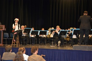 """Claire Ramsey of Oxford (seated on stool at left) narrates during the Vance-Granville Community Band performance of """"'Twas the Night Before Christmas."""" Brian Miller of Louisburg conducts. (VGCC photo)"""