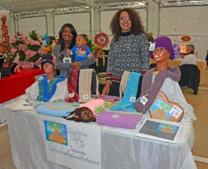 Renee Taylor of Macon (right) is seen here participating in the Handcrafted Holiday Market after completing the NC REAL Professional Craft Artists Entrepreneurship program. At left is her daughter, Angelique Taylor, holding her grandson, Kaiden. Taylor is a mixed media artist who enjoys painting and making hats and scarves. (VGCC photo)