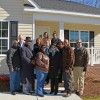 """Posing in front of the newly dedicated home are, in front, from left, Zelodis Jay, chairman of the Granville County Board of Commissioners; Calvin """"CJ"""" Harris, mayor pro tem of Oxford; Kim Simmons; Ruby Powell Greene; Bruce Simmons; and Granville County Habitat for Humanity board member Bonn Williams; on second row, from left, Habitat board member Gloria Boone, Habitat executive director Julie Booth and Habitat board president Cheryl Hart; and in back, from left, VGCC President Dr. Stelfanie Williams and Carpentry program head Keith Tunstall. (VGCC photo)"""