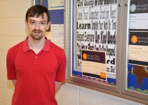VGCC student Andrew Dawson poses next to his Microsoft Office Specialist Master certificate, which hangs, along with those earned by other students, on a bulletin board in Building 7 on the college's Main Campus.  (VGCC photo)