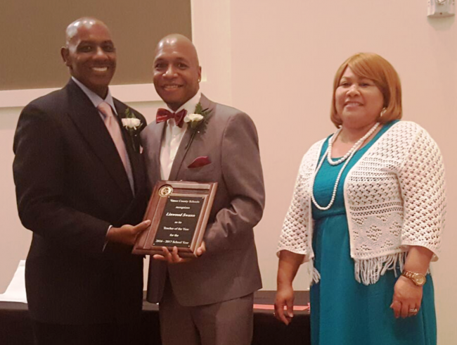 Linwood Swann of Eaton-Johnson Middle School, center, accepts the 2016-2017 VCS Teacher of the Year plaque from Superintendent Anthony D. Jackson and Board Chair Gloria J. White.