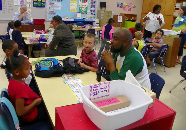 Zeb Vance Principal Kristian Herring, seated in right foreground, and other administrators talk with students in a kindergarten class at Zeb Vance Elementary.