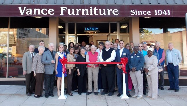 Shown at the Henderson-Vance Chamber of Commerce ribbon cutting for Vance Furniture are, owners Craig and Maria Bailey & Sam and Decie Harper; Dale Abbott, Henry Bryan, Marvin Daniel, Kenny Davis, Mitch Davis, Brenda Faucette, Michael Foster, and Zac Salazar (staff), Mayor Eddie Ellington; Councilwoman Fearldine A. Simmons; Desiree Brooks, Rachel Hedrick, Stephanie Ranes and Diane Robbins, The Daily Dispatch; former Mayor Pete and Grace O'Geary; Miss Kerr Lake Festival, Evan O'Geary; HVCC President, John Barnes; Chamber Ambassador Kevin Bullock, WIZS 1450 Radio; Chamber Ambassador Courtney Morgan, Henderson Wellness Center; Jon Anderson and Sallie White, BB&T; Tommy Roberson, ROBCO Manufacturing; Jenny Hester, PRIM Development & Rentals; Harold and Opie Frazier, Frazco; Carolyn Powell, Downtown Development; Stuart Litvin, EDC; HVCC Work First Coordinator, Vanessa Jones; and other business leaders and friends. Not Pictured: HVCC Office Manager, Melanie Mann; HVCC Director of Membership Services, Annette Roberson.