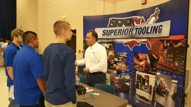 Robbie Earnhardt (center), owner of Wake Forest-based Superior Tooling, talks with students attending Manufacturing Day at VGCC.(VGCC photo)