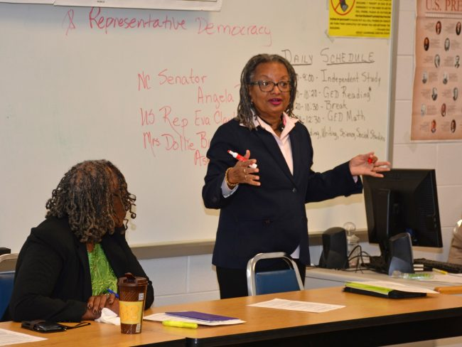 As Dollie Burwell (seated) listens, N.C. Sen. Angela Bryant discusses state government with students at VGCC. (VGCC photo)